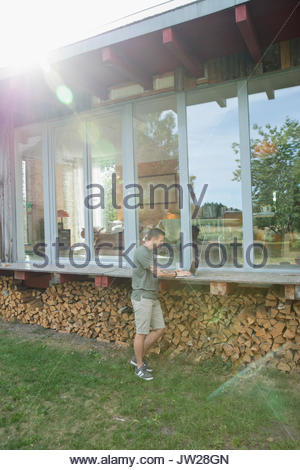 Young man using laptop on wood cabin patio above firewood - Stock Photo