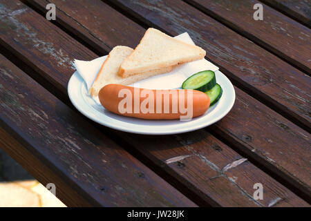 Bock sausage, wieners or Frankfurther sausage with toast and cucumbers on a white plate. - Stock Photo