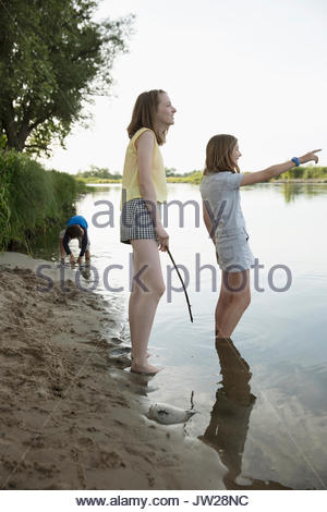 Curious girls pointing in summer lake - Stock Photo