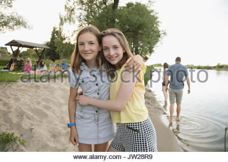 Portrait smiling pre-adolescent sisters hugging on summer lakeside beach - Stock Photo
