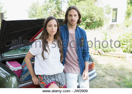 Portrait serious young couple unpacking car - Stock Photo