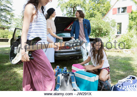 Friends arriving at summer house, unloading car and playing guitar - Stock Photo