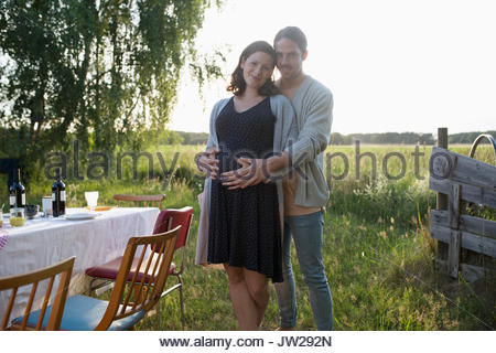 Portrait affectionate pregnant couple hugging at garden party dinner in rural summer yard - Stock Photo