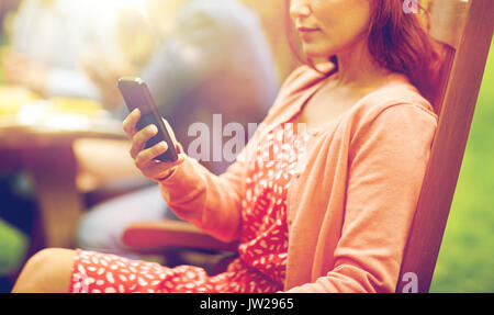 woman with smartphone and friends at summer party - Stock Photo