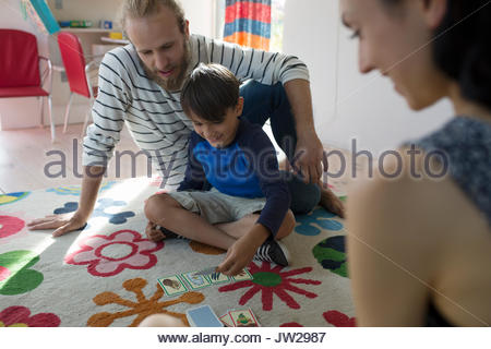 Family playing card game on pattern rug - Stock Photo