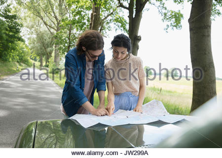 Young couple looking at map on automobile hood of car on rural road - Stock Photo