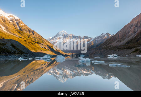 Sunrise, reflection in Hooker Lake, morning sun illuminating Mount Cook, Mount Cook National Park, Southern Alps, - Stock Photo