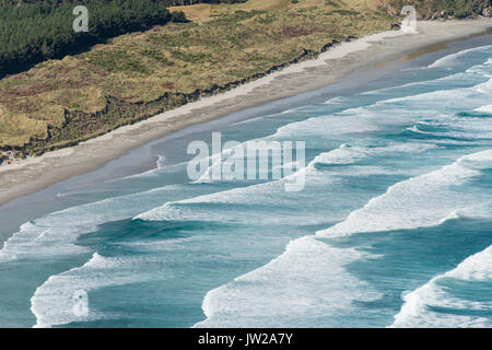 Spinning waves breaking at the flat sand beach, Allans Beach, Dunedin, Otago Peninsula, South Island, New Zealand - Stock Photo