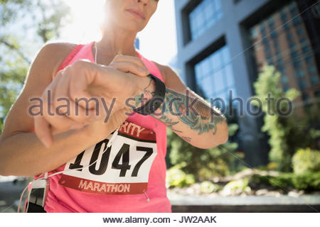 Tattooed female marathon runner checking smart watch in urban park - Stock Photo