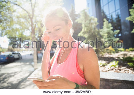 Smiling mature female runner listening to music with earbud headphones and mp3 player in sunny urban park - Stock Photo