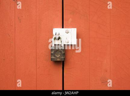 a metal padlock protecting locking two wooden doors outside; UK - Stock Photo