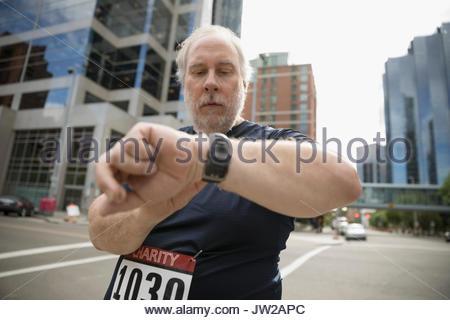 Mature male marathon runner checking smart watch on urban street - Stock Photo