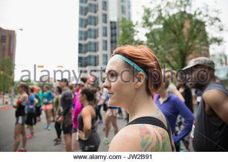 Female marathon runner looking away on urban street - Stock Photo