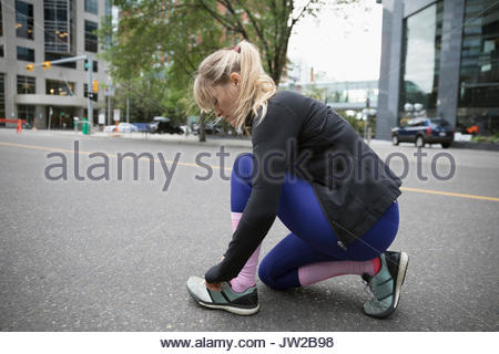 Female runner tying shoelace on urban street - Stock Photo