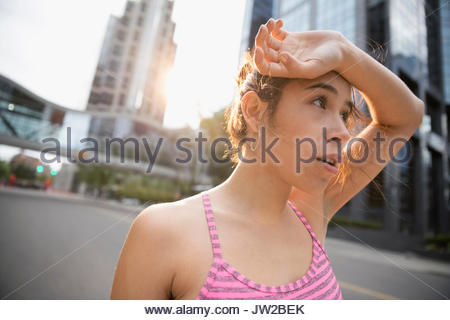 Tired young female runner wiping sweat from forehead on urban street - Stock Photo