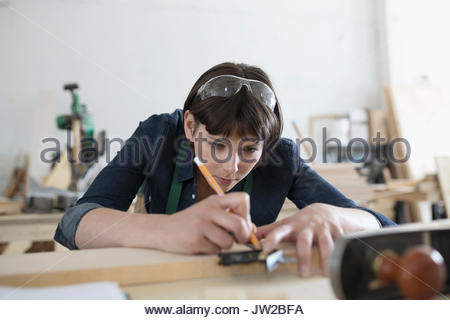 Focused female carpenter measuring and marking wood with pencil in workshop - Stock Photo