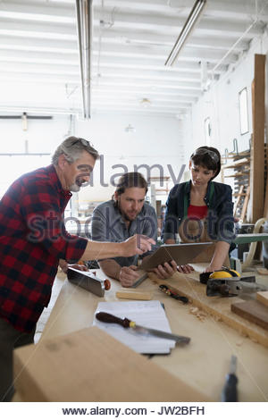 Carpenters using digital tablet at workbench in workshop - Stock Photo