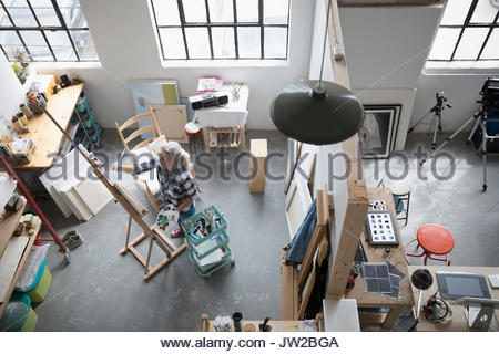View from above female painter painting at canvas on easel in coworking space art studio - Stock Photo