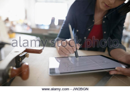 Female carpenter sketching with digital tablet stylus at workbench in workshop - Stock Photo