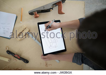 View from above female carpenter sketching with digital tablet stylus at workbench in workshop - Stock Photo