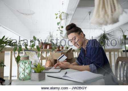 Female plant shop owner with credit card paying bills online at laptop in workshop - Stock Photo