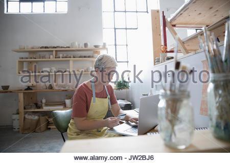 Female potter online shopping, ordering supplies with credit card at laptop in art studio - Stock Photo