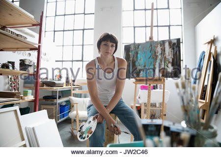 Portrait confident, serious female painter with palette painting at canvas on easel in art studio - Stock Photo