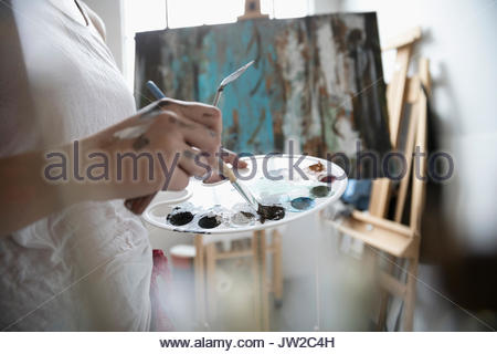 Close up female painter dipping paintbrush into palette, painting at canvas - Stock Photo