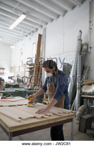 Male carpenter wearing protective mask and using sander to sand wood planks in workshop - Stock Photo