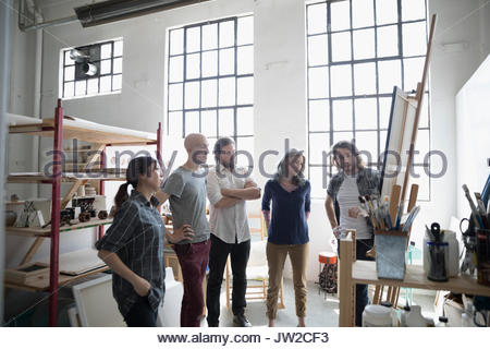 Painter students in painting class discussing canvas painting on easel in art studio - Stock Photo
