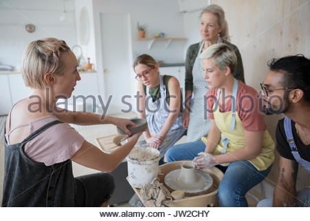 Female instructor explaining process to pottery students at pottery wheels in art studio - Stock Photo