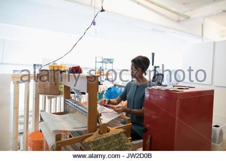 Female weaver weaving at loom in art studio - Stock Photo
