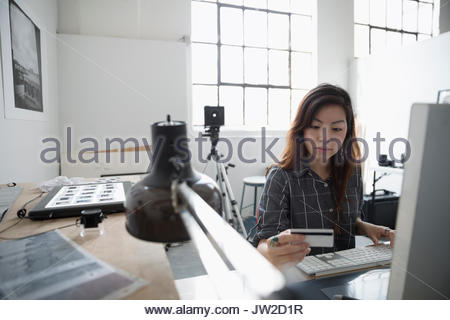 Female photographer online shopping at computer, ordering with credit card in art studio - Stock Photo