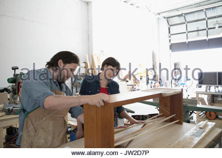 Carpenters examining wood bench on workbench in workshop - Stock Photo