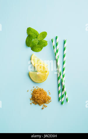 Mojito ingredients. Lemon, mint and cane sugar blue background. Sweet sugar, mint leaves, lemon and striped straw. - Stock Photo