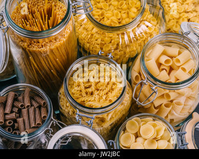 Photo of different pasta types in large glass jars. - Stock Photo