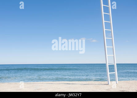 White ladder on empty beach with blue ocean in background - Stock Photo