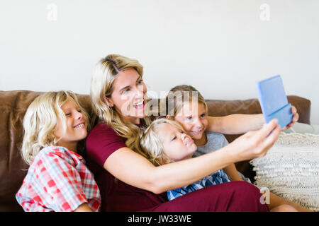 Mother and children (4-5, 6-7, 8-9) taking selfie with digital tablet - Stock Photo