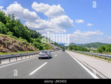 Cars speeding on the Autobahn among mountain scenery. - Stock Photo