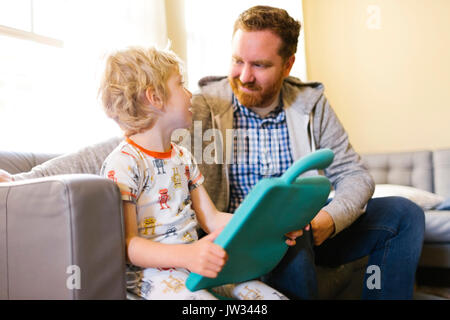 Father and son (4-5) playing with electronic toy - Stock Photo