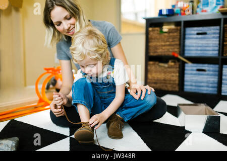 Mother learning son (4-5) to tie shoes - Stock Photo