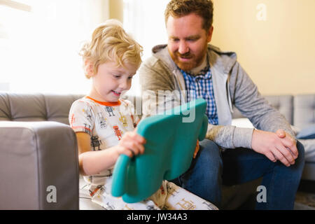 Boy (4-5) and man using digital tablet on sofa in living room - Stock Photo