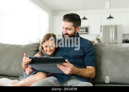 Father with daughter (6-7) using digital tablet in living room - Stock Photo