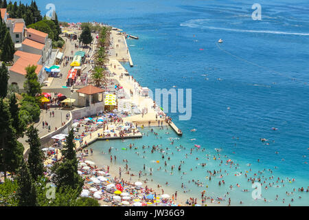 NEUM, BOSNIA AND HERZEGOVINA - JULY 16, 2017 : A view of the town waterfront and people swimming and sunbathing - Stock Photo