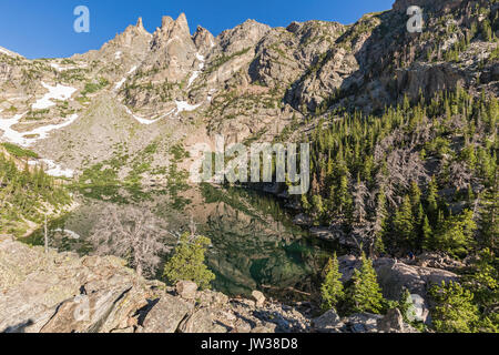 Snow below the spires near Flattop Mountain reflected in perfectly still green waters Emerald Lake in Rocky Mountain - Stock Photo