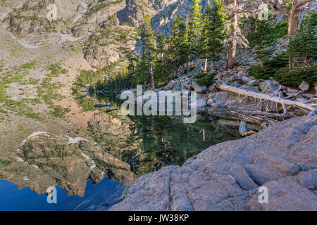 Snow below Flattop Mountain reflected in perfectly still Emerald Lake in Rocky Mountain National Park, Colorado - Stock Photo