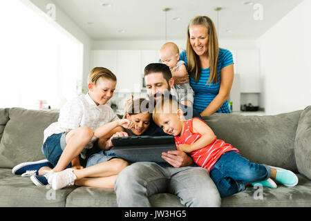 Family with four children (6-11 months, 2-3, 6-7) using digital tablet - Stock Photo
