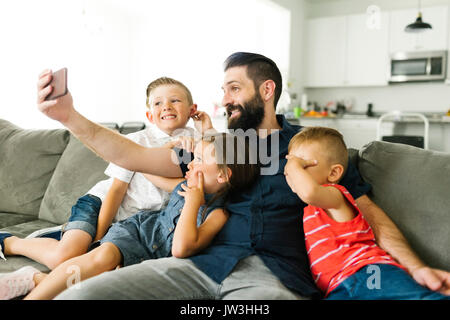 Father with his three children (2-3, 6-7) taking selfie with smart phone - Stock Photo