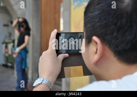 asian tourists taking pictures of each other downtown a historic city center  in Europe, Bolzano, Italy, South Tyrol - Stock Photo