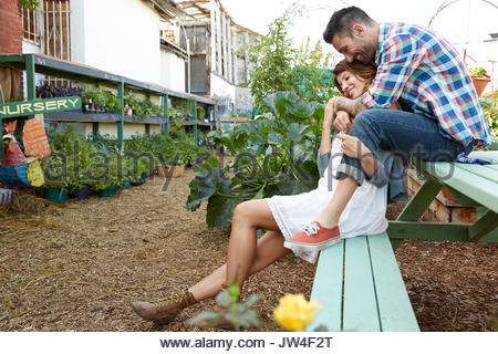Affectionate couple hugging on bench in plant nursery - Stock Photo